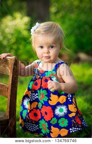 one blonde caucasian toddler learns to stand holding onto chair outside