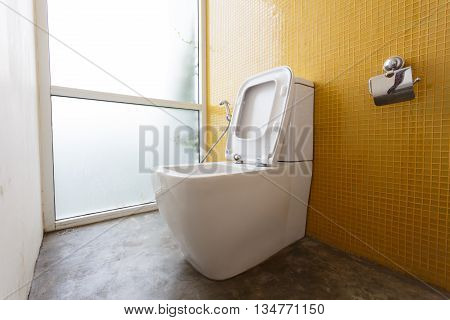 White Flush Toilet And Yellow Wall Mosaic Decoration In Modern Bathroom Interior Home