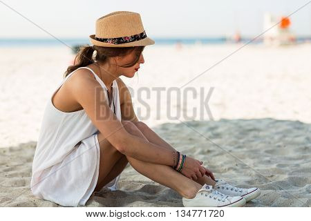 Stylish Woman Sitting On A Sandy Beach At Summer