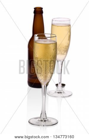 Two glasses of home-brewed cider with a bottle against a white background.
