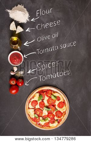 Ingredients for pizza on the chalkboard (tomatoes cheese sauce water spices oil and flour). Reciepe of classical italian pizza