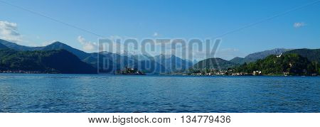 View of the calm lake Orta (Lago D'Orta) and the snow covered mountains of the Parco Nazionale della Val Grande in the background. The historic island and township of San Giulio are located at the shore of the lake at the foot of forest covered hills. Pie