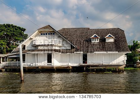 Old Chao Phraya River Thai traditional house village riverfront in Bangkok Thailand.