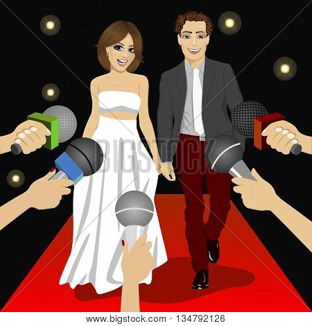 Young fashionable couple on a red carpet event before press reporters