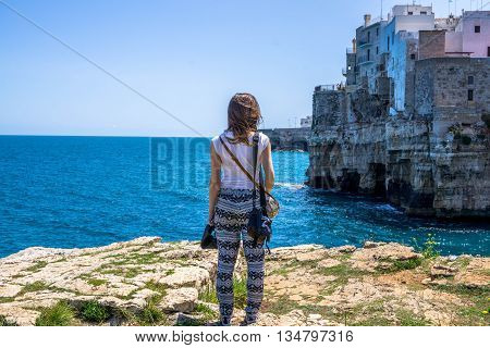 Woman standing in front of the sea in Polignano a Mare, Puglia region. Old town made on rocks. Beautiful Italy. Travel concept