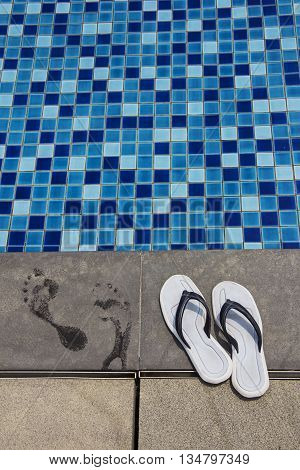 Pair of blue flip-flops and footprints on the swimming pool side