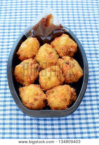 Fresh vegetable pakoras with tamarind chutney prepared by the delicatessan in plastic container on blue and white check cloth in vertical format