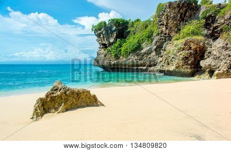 A deserted tropical beach with rocky headland the horizon and a cloudy sky.