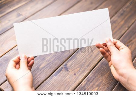 woman hold white bland paper on table