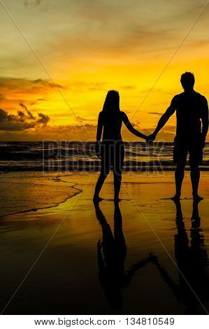 A Couple at the beach for sunset as the sun goes down it casts a beautiful orange colour over the sky and creates a reflection on the wet sand