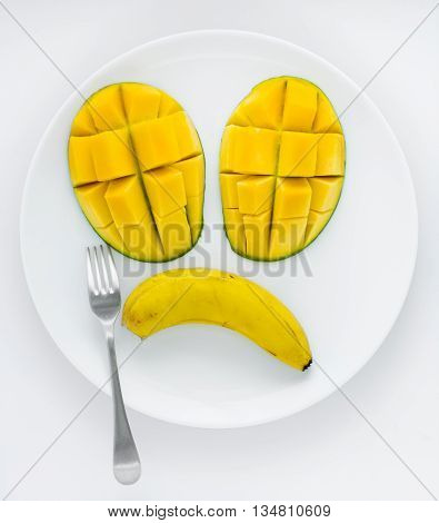 A sad face made from mangoes and a banana on a white plate with white background and a fork.