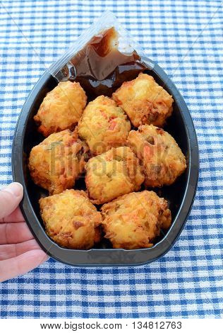 Fresh vegetable pakoras with tamarind chutney prepared by the delicatessan in plastic container on blue and white check cloth in vertical format with hand