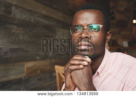 Attractive Young Black Writer In Pink Shirt, Sitting At A Cafe With Dreaming Face Expression, Lookin