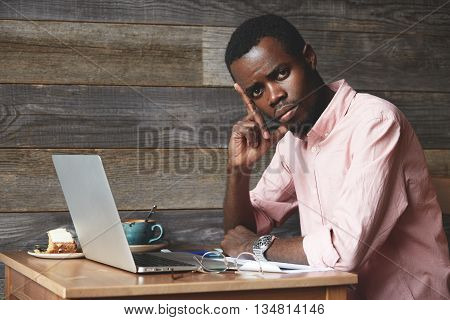 Tired Black Male Sitting At A Cafe After A Hard Workday, Touching His Head Because Of Bad Headache,