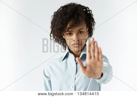 African Woman With Curly Hair Wearing Striped Shirt, Showing Stop Gesture With Her Left Hand, Posing