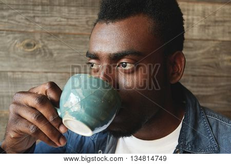 Close Up Portrait Of African-american Person Drinking A Cup Of Tasty Coffee In The Morning. Young Ma