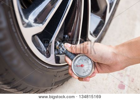 Close-Up Of Hand holding pressure gauge for car tyre pressure measurement