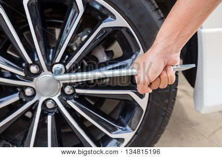 Hands disassembling a modern car wheel (steel rim) with a lug wrench for change wheel
