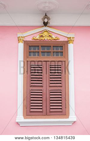 A beautiful classic window on pink wall in Sino-Portuguese style at Soi Rommanee Phuket Thailand
