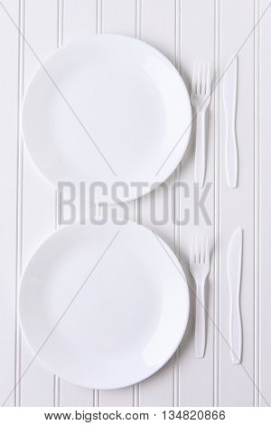 Top view of an all white place setting. White plates and plastic utensils on a white background.