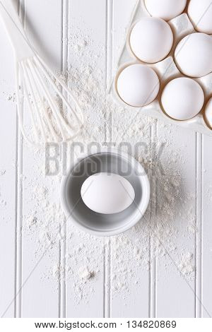 White on White baking still life. Top view of items for baking: eggs, flour and a whisk on a white beadboard surface.