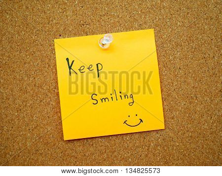 Keep smiling in post note on wooden board