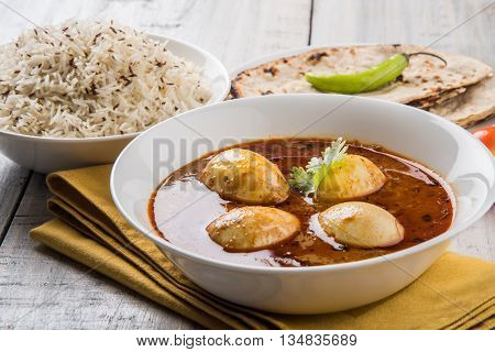 egg curry with roti/chapati and jeera rice, tasty and spicy anda curry with roti and rice, indian egg masala curry served in ceramic bowl with roti, salad and jeera rice