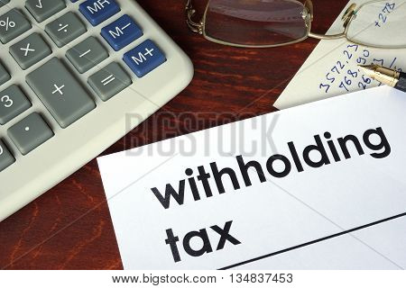 Withholding tax written on a paper. Financial concept.
