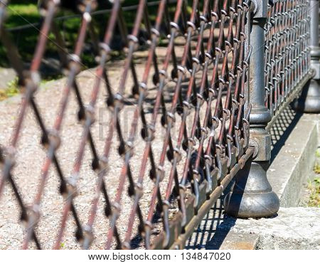 indistinct fragment of an old iron fence closeup in park in outdoor and a blank space
