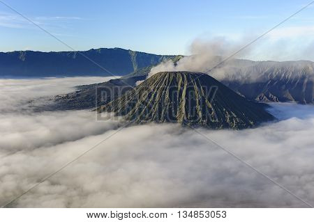 Beutiful misty morning view of Mount Bromo in Tengger Semeru National Park East Java Indonesia during beutiful sunrise with the valley full of sea cloud.
