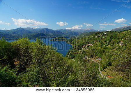 Mediterranean landscape. View of mediterranean lake Orta (Lago d'Orta) from the Torre di Buccione. Snow covered mountains and densely forested hills spotted with houses steeply descending to the lake shore in the valley.