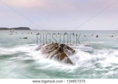 Surfers at Currumbin Rock Gold Coast with ocean current rushing against a large rock on overcast day.