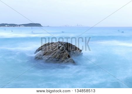 Twilight at Currumbin Rock Gold Coast with ocean current rushing against a large rock on overcast morning.
