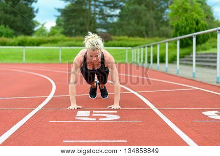 Single Woman Stretching Calf Muscles At Race Track