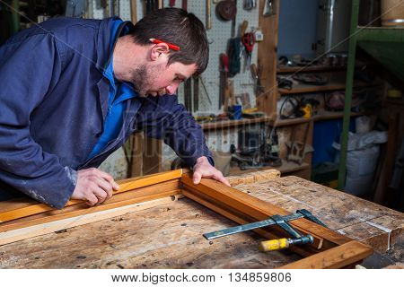 Carpenter Working On A Wooden Window Frame In His Workshop