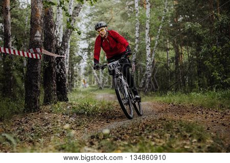 Chelyabinsk Russia - June 5 2016: male athlete a cyclist riding turn in woods during cross-country race