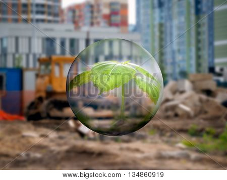 A transparent sphere with a young plant on a background of a construction site. Tractor wasteland. The new city quarter. Concept - urban environment the destruction of green areas