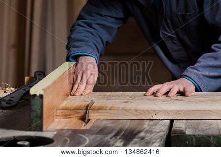 Carpenter's Hands Cutting Wood Board With Table Saw