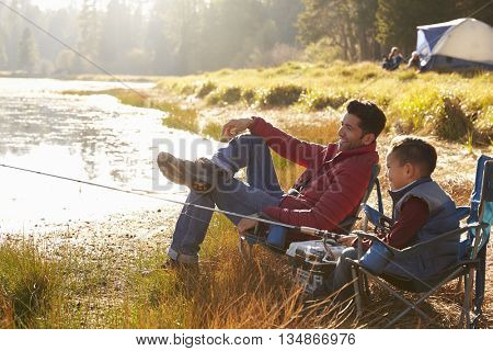 Father and son on a camping trip fishing by a lake