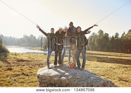Portrait of five friends standing on a rock in countryside