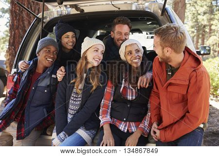 Friends sitting in the open back of a car look at each other