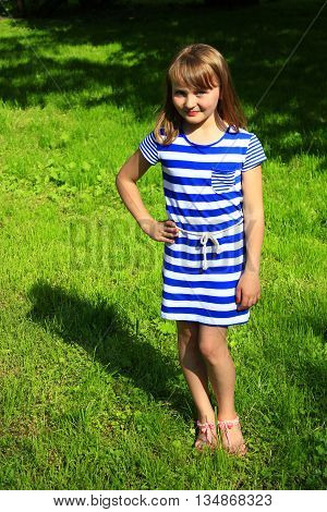 sympathetic little fashionable girl lies on the green grass