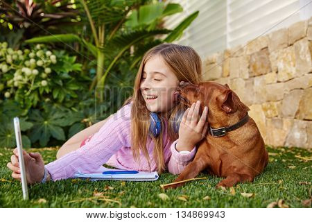 Blond kid girl selfie photo with tablet pc and dog lying on grass