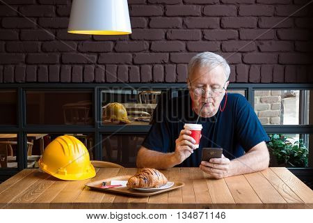 Senior construction foreman taking refreshment break drinking coffee and checking his phone