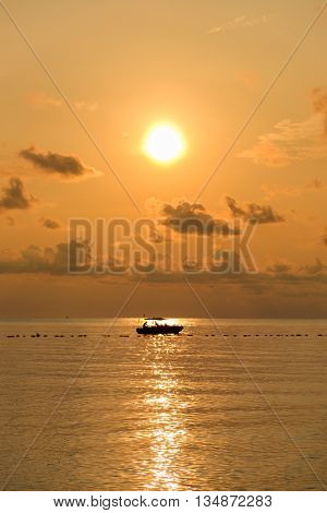 Seascape of sea during sunrise with silhouette of small boat at Ao Lung Dam beach in Samet island Thailand.