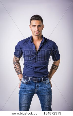 Handsome young man in blue shirt and jeans posing isolated on white background in studio