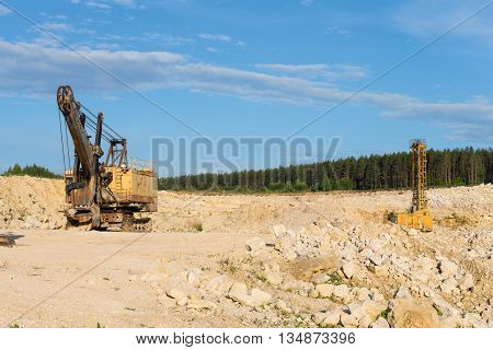 stone crusher in a quarry. mining industry. repairing service on excavator