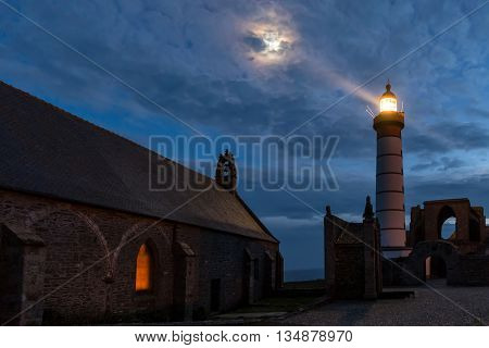 Mystical chusrch and lighthouse illuminated with moon over cloudy sky at Saint Mathieu point, Brittany, France
