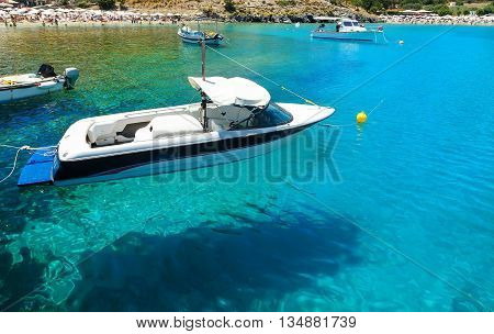 floating in the water Boat on the background of the beach and bathing people in the Bay of Lindos, Rhodes Greece