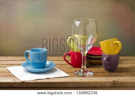Still life with colorful tableware on wooden table over grunge background